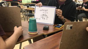 Students reviewing each other's math problems written on small whiteboards