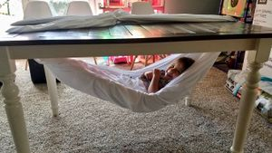 A child lies in a hammock under a table.