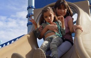 A fourth-grade student from McKinley Elementary School in Santa Monica slides down a slide with her buddy, a fellow student with special needs, during a field trip to a local playground.