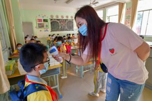 A teacher checks a student's body temperature at the entrance of a classroom at Haikou Qiongshan No.5 Primary School on April 20, 2020 in Haikou, Hainan Province of China
