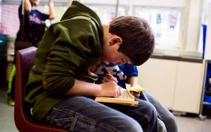 A student reads a book in his class.