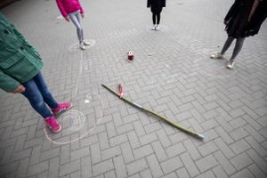 Schoolgirls stand in the corners of a square of chalk to observe the rules of distance on the playground of the Goldbeck School.