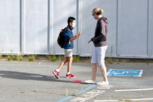 A student low-fives his mother goodbye before heading into school at San Jose Middle School.