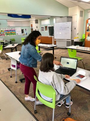 Candice Aguirre, a science teacher at Marin's Community School, works with a student. Classrooms were restructured to create more space between desks.