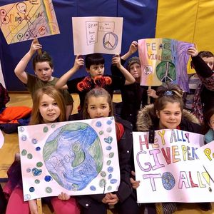 New Jersey students hold up signs during the peace sign project.