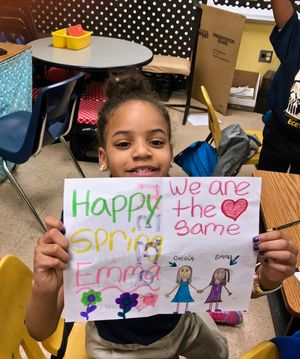 A student holds up a letter she received from her pen pal in New Jersey.
