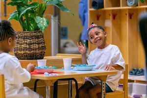 A child eats a meal with a classmate at Clayton Early Learning Center in Denver.