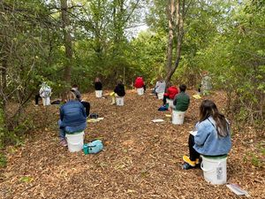 Students sitting on plastic buckets in outdoor classroom at Marshwood Great Works School