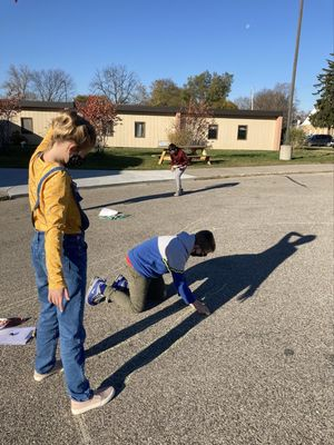 Elementary students conduct a shadow experiment outside