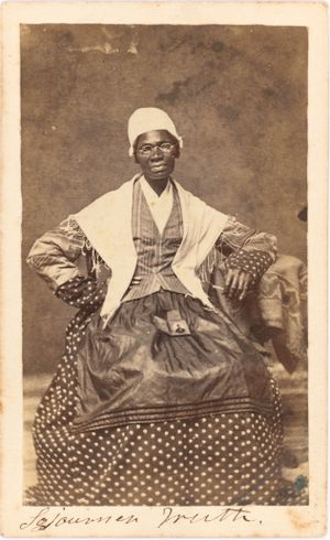 Photo portrait of Sojourner Truth seated with photograph of her grandson, James Caldwell of Co. H, 54th Massachusetts Infantry Regiment, on her lap