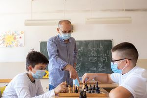 Photo of two boys playing chess at school during COVID-19 pandemic
