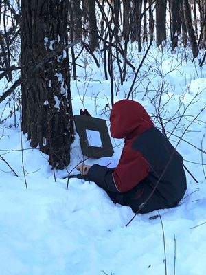 A student journals by a tree.
