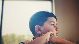 A teen boy looks out a window