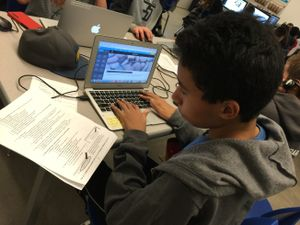 Student using a laptop and textbook