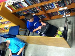 Two students are sitting on a classroom floor.