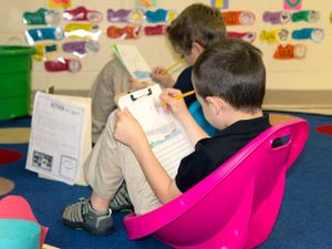 Two young boys writing on clipboards in small rocking chairs