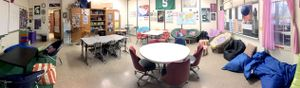 A deskless classroom filled with tables and non-traditional furniture like bean bags.