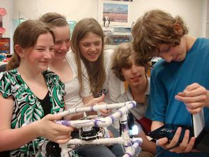 Five students smiling in a classroom, huddling together next to a small computer and a square contraption made of white plastic pipes.