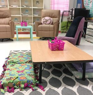 A low classroom table with floor pillow seating