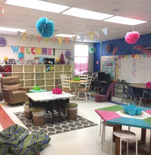 A classroom with different shaped tables and non-traditional seating, like bucket chairs and shoe-shaped chairs