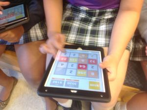 A girl plays a math game on her iPad.