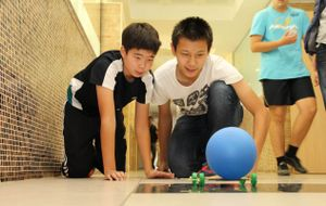 Two boys are kneeling in a school hallway, watching a blue ball roll on a paper-stick contraption with wheels.