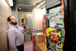 Tour guest photographs server room with his cell phone.