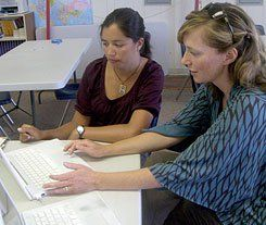 Two women sitting next to each other at a desk working on a laptop