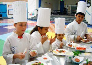 Four kids wearing white chef coats and hats cooking at a long table.
