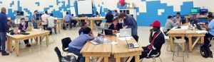 A panoramic view of a large classroom. The walls are painted in white and blue blocks, like a digital screen. Five groups of students are sitting at sets of rectangular, wood tables pushed together. They're all working on laptops.