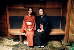 Two beautiful women sitting on a bench in Kyoto