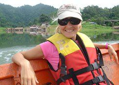 Woman wearing a baseball cap, sun glasses, and a life vest sitting, leaning back in a boat