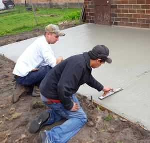 Two boys smoothing out a just-poured concrete slab next to the house