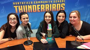 "Five girls are sitting at a table with microphones behind a backdrop that says, ""Northfield Community School Thunderbirds."""