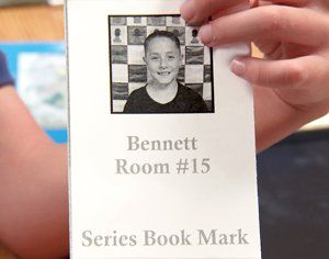 Boy holding his Series Book Mark that shows his picture, name, and room number