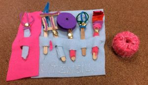Six Pirate tool utensils make from popsicle sticks and pipe cleaners laid out in a row on a large piece of felt which can be rolled up