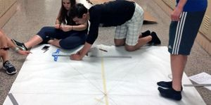 A teenage boy is kneeling on the floor in a school hallway beside a large piece of paper. He's drawing straight lines on it against a metal ruler. A teenage girl is sitting beside him, cutting something with scissors. Two other teenagers are watching.