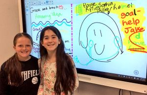 Two girls standing in front of an electronic whiteboard