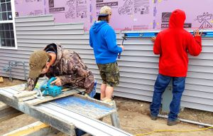 One boy at a table saw and two boys leveling and installing siding on the house