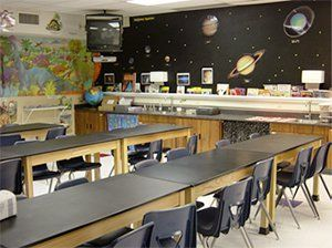 An empty science classroom with three, long tables and a space backdrop against one wall and a dinosaur backdrop against the adjacent wall.