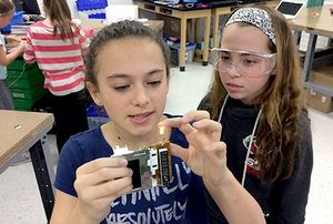 A girl is holding a student-made electronic device that has lit a small light bulb. Another girl in protective goggles is standing next to her.
