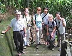 Six people standing together on a bridge, five wearing backpacks and cameras