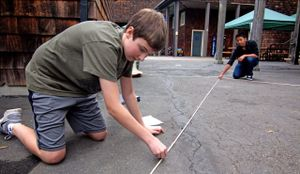 Two boys using measuring tape and chalk on the school grounds