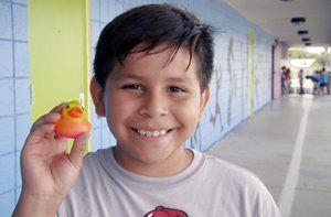 Boy holding up a rubber duck toy he picked as a reading winner