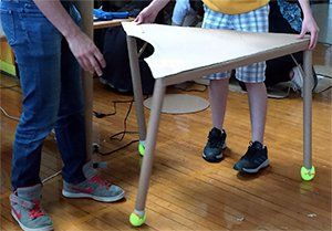 Two students are holding up a cardboard-made desk. The desk looks wobbly with two legs off-center.