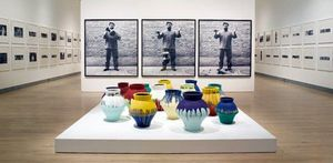 Three full length pictures behind a display of 15 colorful pots of Ai Weiwei holding, dropping an urn, and seeing the pieces on the ground