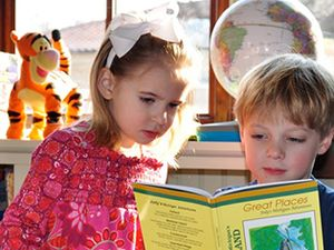 Two young children reading together