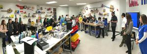 Panoramic shot of students standing around work tables listening as four adults speak. There are projects on the walls, and lots of tools, bins, and notebooks all over the tables.
