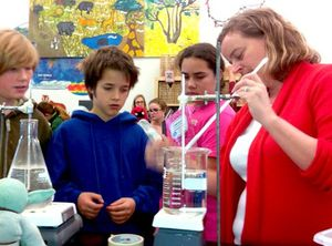 Teacher stirring a liquid in a beaker on a Bunsen burner with three students looking on