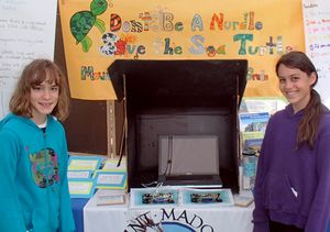 Two girls standing at a booth that has lots of reading material and turtle facts up on the walls